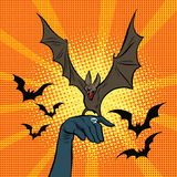 Evil bat sitting on the hand. Pop art retro vector illustration. Halloween and witchcraft witches Stock Photo