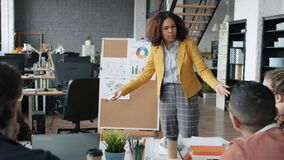 Evil boss Afro-American businesswoman yelling at subordinates during business meeting in office
