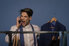 Evil boss. Man talk angry on smartphone with jacket in shirt, tie. Businessman use phone in closet on blue background. Shopping, sale, purchase. Fashion, style stock photography