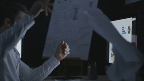 Evil business man throwing data document on computer table in dark office. Stressed business analyst working late in night office. Exhausted man having problem stock video footage