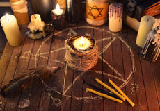 Evil candle in pentagram circle. Warlock or evil burning candles on wooden background with pentagram circles. Black magic ritual. Scary still life with occult royalty free stock image