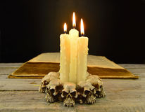 Evil candles with book Royalty Free Stock Photography