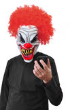 Evil Clown. A clown with scary teeth,red hair staring a mobil phone royalty free stock photos