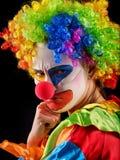 Evil clown on black background. Portrait of crazy woman. Stock Photos