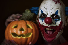 Evil clown with a carved pumpkin Stock Image