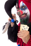 Evil clown holding a Knife and playing cards,  on white Stock Photos