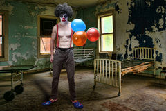 Evil Clown Inside Condemned Room With Hospital Bed. Scary Evil Clown Inside Condemned Room With Hospital Bed royalty free stock images