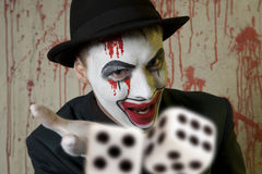 Evil clown playing with dice Royalty Free Stock Photos