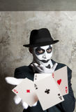 Evil clown playing with poker cards Stock Image