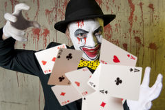 Evil clown playing with poker cards Royalty Free Stock Photo