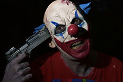 Evil clown pointing a gun to his temple Royalty Free Stock Image