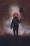Evil clown standing with a black balloon against a dark background Royalty Free Stock Image