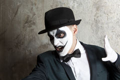 Evil clown wearing a bowler hat on wall background Royalty Free Stock Image