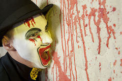 Evil clown wearing a bowler hat on wall Stock Photos