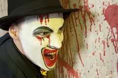 Evil clown wearing a bowler hat on wall Royalty Free Stock Photography