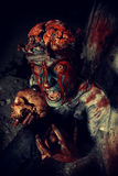 Evil and darkness. Bloodthirsty zombie chewing the skull of his victim. Halloween concept Stock Photography