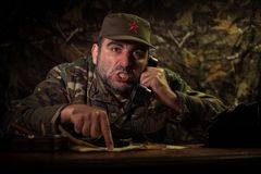 The evil dictator sitting on table. Angry communist general sitting at headquarter or Cuban commander in dark room. Studio decoration royalty free stock images