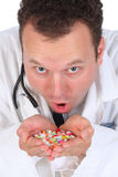 Evil Doctor Giving Many Pills Stock Photo