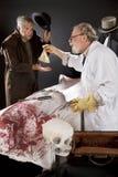 Evil doctor pays graverobber Stock Photo