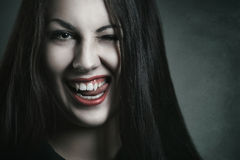 Evil expression on vampire face. Evil and amused expression on beautiful vampire face . Halloween and horror stock photography