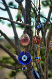 Evil eye charms hang from a bare tree in Cappadoci Stock Photography