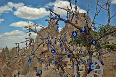Evil eye charms hang from a bare tree in Cappadoci