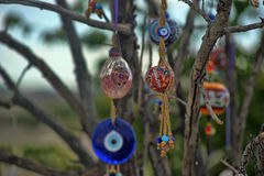 Evil eye charms hang from a bare tree in Cappadoci Royalty Free Stock Photography
