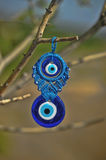 Evil eye charms hang from a bare tree in Cappadoci Royalty Free Stock Images