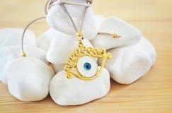 Evil eye necklace on white stones Royalty Free Stock Photo