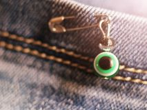 Evil eye on a pin on jeans. Evil eye on a pin on blue jeans royalty free stock photography