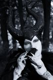 Evil fairy tale, maleficent, malevolent queen with horns and crow feather gown. Evil fable queen with evil, malevolent and maleficent black horns Royalty Free Stock Images