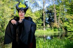 Evil fairy tale, maleficent, malevolent queen with horns and crow feather gown. Evil fable queen with evil, malevolent and maleficent black horns Stock Photo