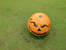 Evil face on orange round shape rock Royalty Free Stock Photography