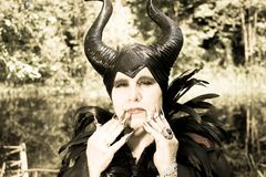 Evil fairy tale, maleficent, malevolent queen with horns and crow feather gown Royalty Free Stock Images