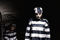Evil female prisoner wearing  prison uniform standing near bed w Stock Image