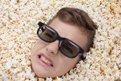 Evil ferocious young boy in stereo glasses looking out of popcorn Royalty Free Stock Photos