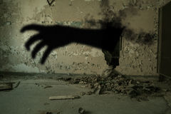 Evil Hand Coming Out of Hole in Wall Stock Photography