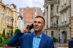 A evil and handsome businessman in a city talking by phone. royalty free stock photos