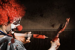 Evil Healthcare clown holding needle and syringe Stock Photos