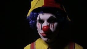 Evil, horror clown man looking into camera.