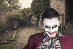 Evil joker laugh. Joker face with the cemetery gate in the background Stock Photo