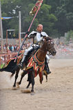 Evil Knight. A scowling knight in armor rides horseback across a tournament field while carrying a standard Stock Photography