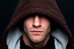 Evil looking hooded man. An evil looking man wearing a hooded top with his eyes hidden against a black background royalty free stock photos