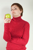 Evil looking woman holding a green apple Stock Image