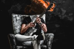 Spicy music - guitarist sitting on a black and silver chair, playing the instrument. Evil, mad guitarist sitting on a black and silver chair, playing the stock photos