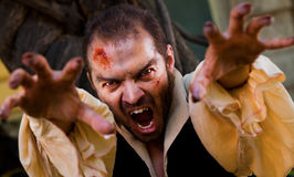 Evil male vampire. Reaching hands to the camera and roaring Stock Photo