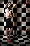 Evil malicious zombie girl with bloody pruning saw Stock Photography