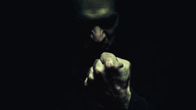 Evil Man With the Fist. Dark person showing the fist. Man full of hate and evil eyes Royalty Free Stock Photography
