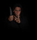 Evil man gesturing silence while holding a knife royalty free stock images