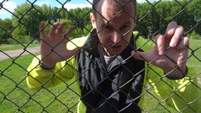 Evil Man in his 20s, leaning against the fence, trying to get out.  stock footage